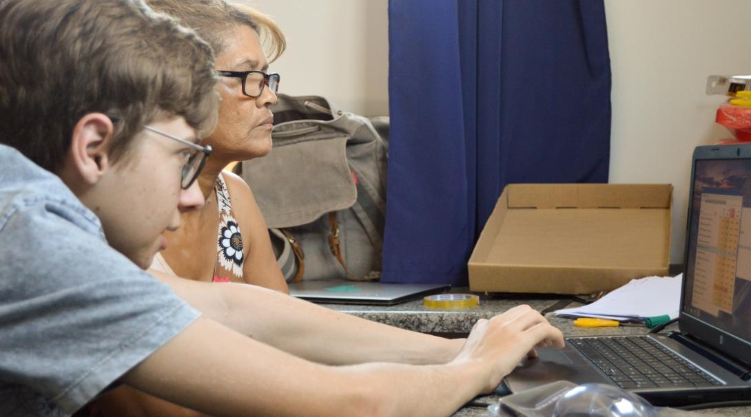 Una mujer local aprendiendo a utilizar el ordenador con uno de nuestros voluntarios en Sudáfrica.
